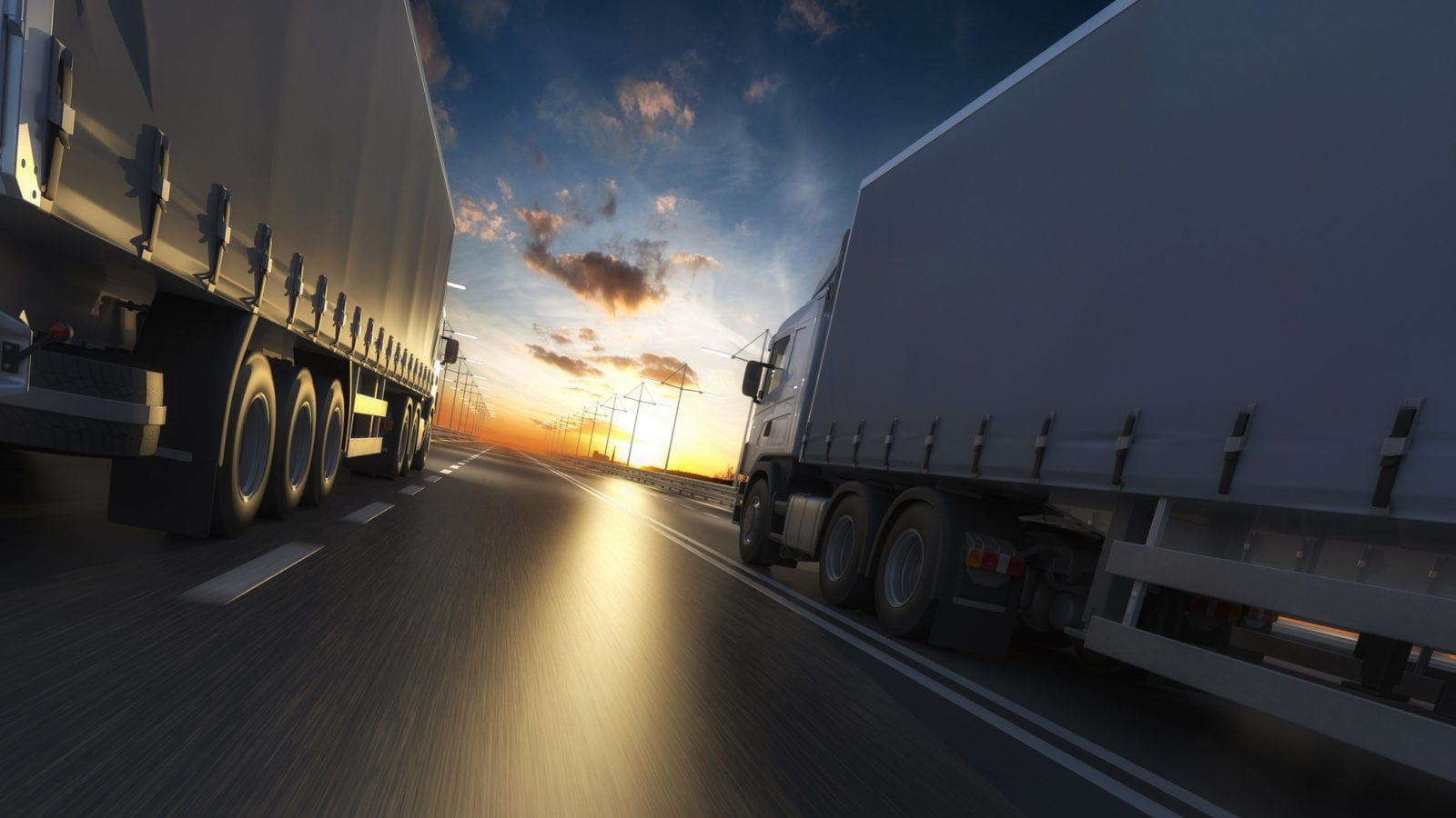 Large Semi-trucks Driving Adjacent To Each Other At Night Stock Photo