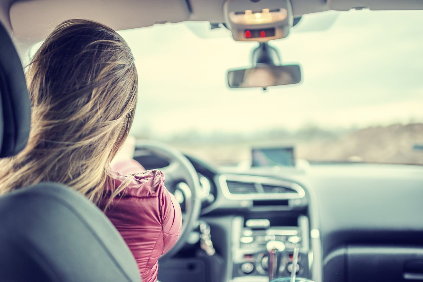Woman Driving Her Car During The Day Stock Photo