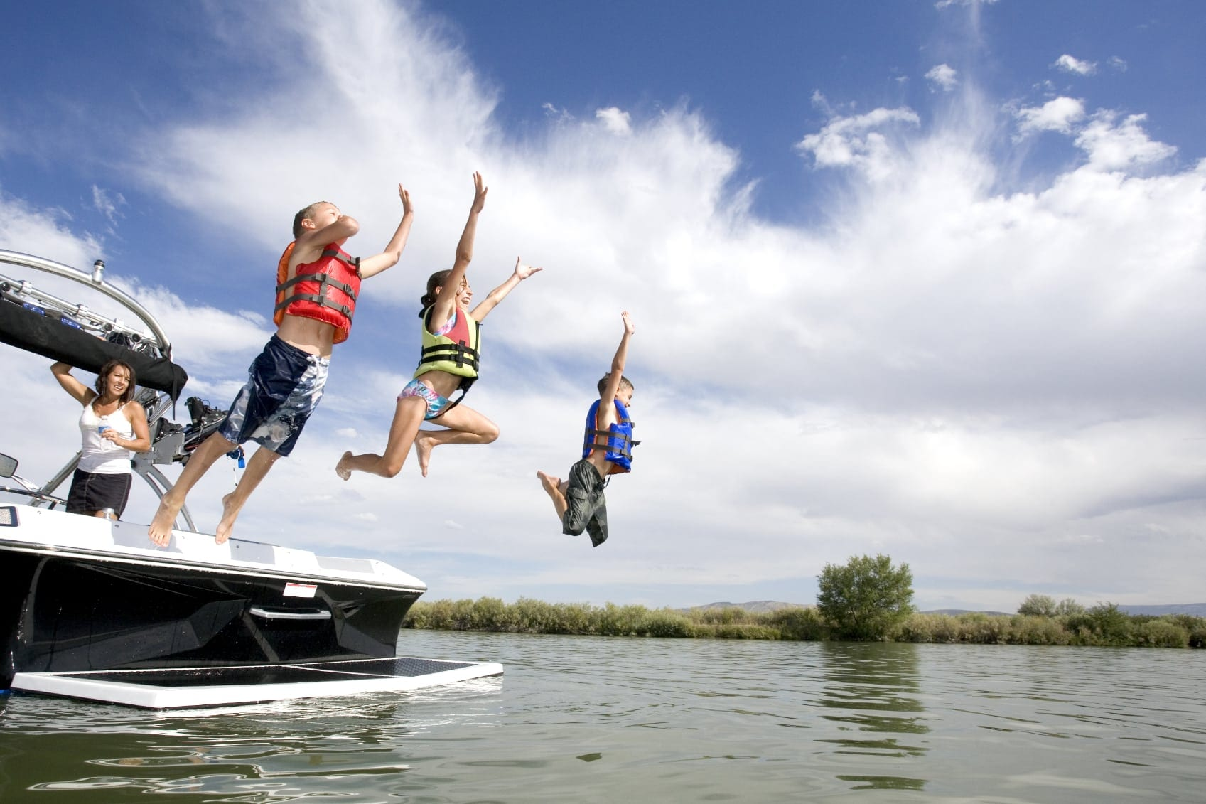 Children Jumping Off Of Family Boat Into Lake Stock Photo