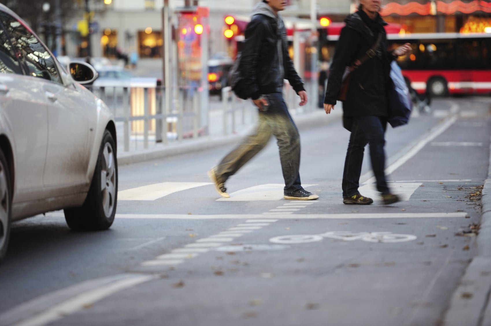 Male and Female Crossing A City Street Stock Photo