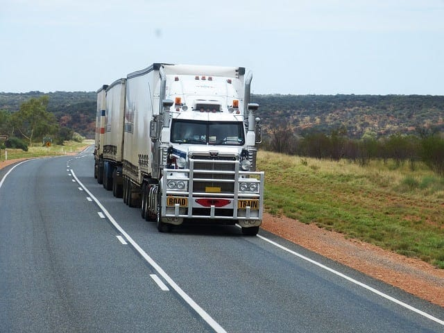White 18-wheeler Truck Driving On A Rural Highway Stock Photo