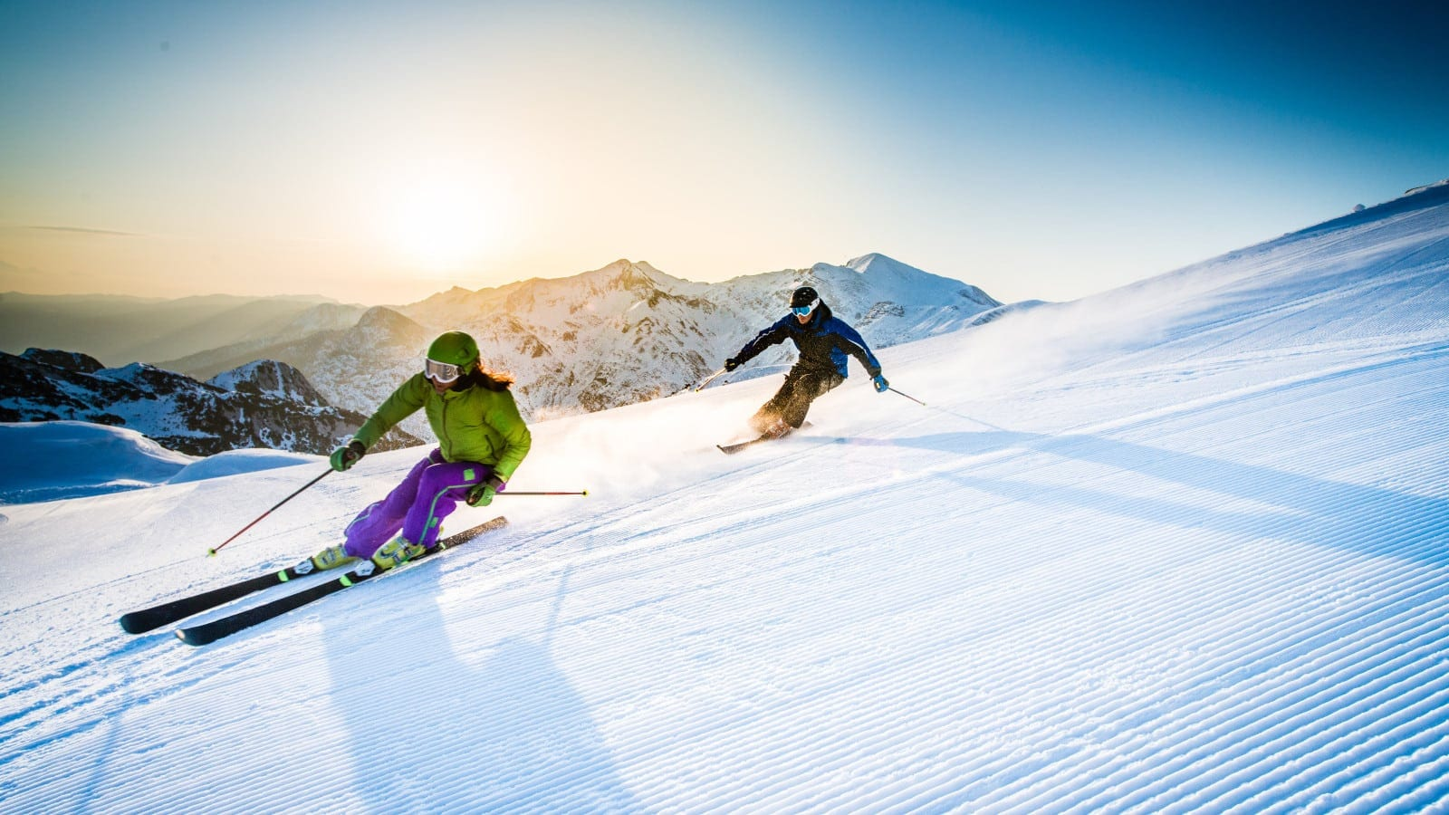 Friends Skiing Down A Large Slope Stock Photo