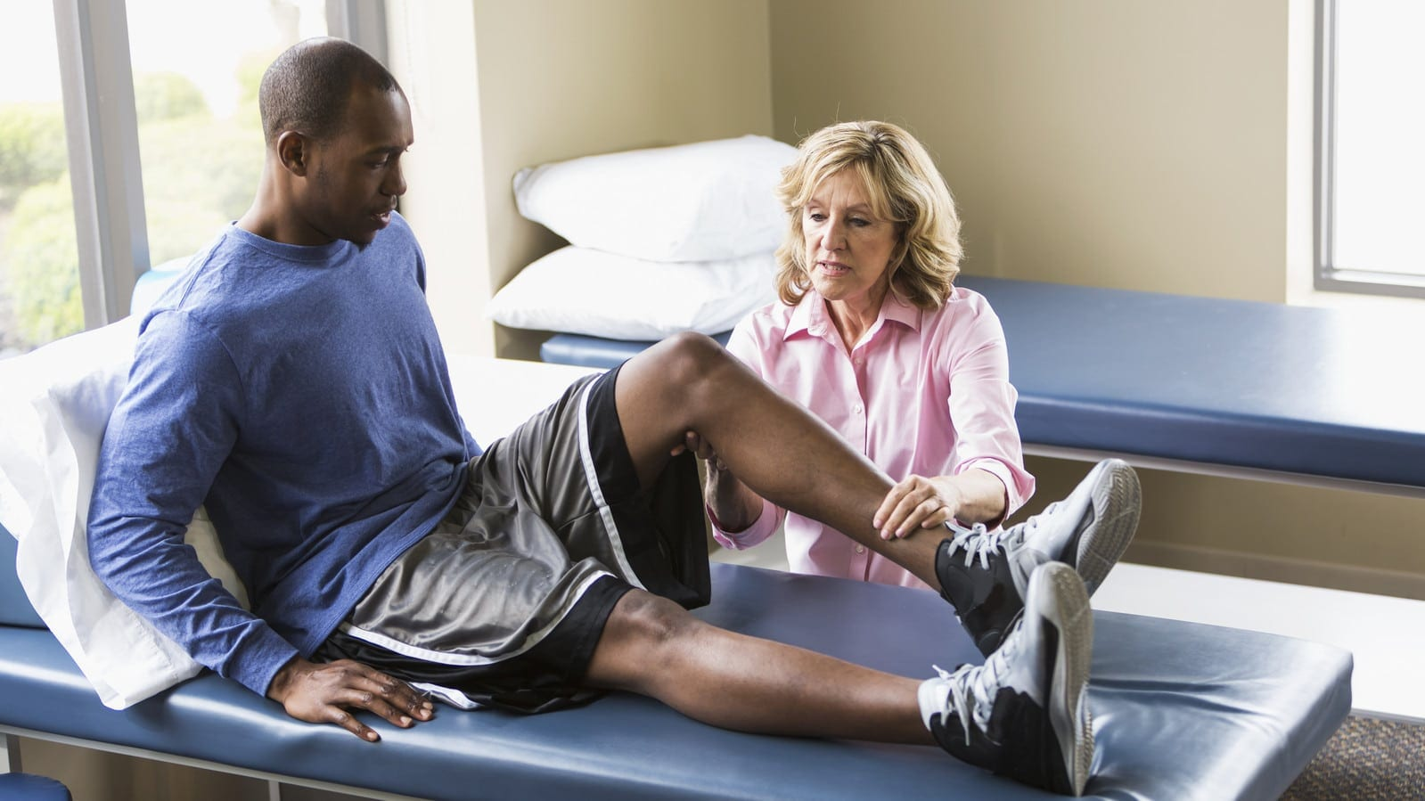 Female Physical Therapist Working With Male Patient Stock Photo