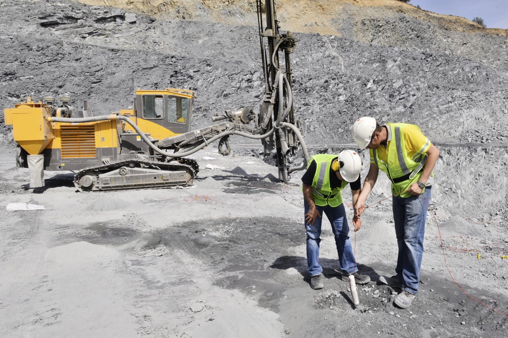 Workers In Hard Hats Using Dynamite On A Job Site Stock Photo