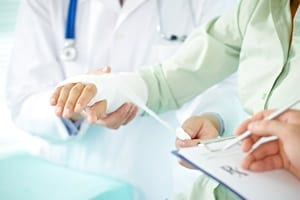 Woman With Wrist Injury Having Arm Examined By Doctor